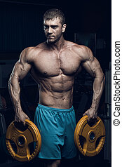 Male bodybuilder, fitness model trains in the gym