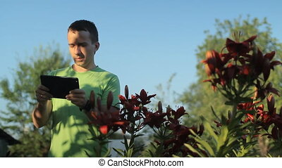 A young man is playing on a tablet near flowers early in the morning
