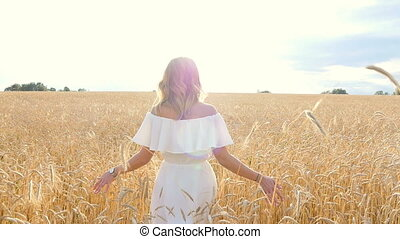 Beautiful young woman in white dress on wheat field -...