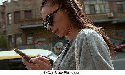 Brunette woman is distracted with texting while standing by...