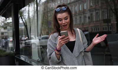 Astonished woman reading sms on her mobile phone with a look of shock and amazement and her mouth hanging open as she stands on a busy urban street with traffic