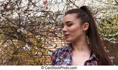 Spring fashion girl in checkered shirt outdoors portrait in blooming trees.