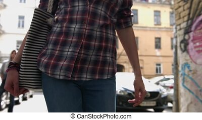 Woman in a checkered shirt, blue jeans and bag walking on the street, concept of Street fashion