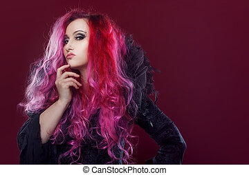 Scary witch with red hair performs magic on a pink...