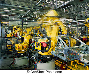 car production line - yellow robots welding cars in a...