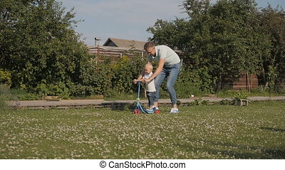 Dad Teaching Son To Ride Kick Scooter Outdoors In The Garden