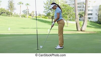 Woman golfer cheering as she sinks her putt - Woman golfer...