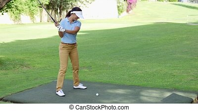 Young female golfer preparing to tee off at the start of a...