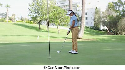 Woman golfer lining up for a putt on the green viewed from...