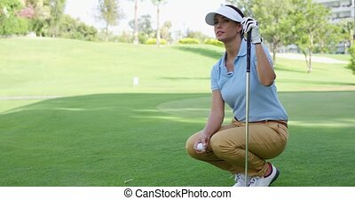 Woman wearing white visor and blue polo shirt squats on golf...