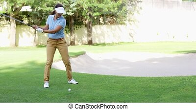 Woman golfer about to play a stroke on the green lining up...