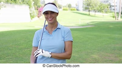 Female golfer wearing visor and blue polo shirt smiles at...