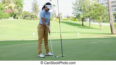 Woman golfer about to sink her putt lining up her ball with...