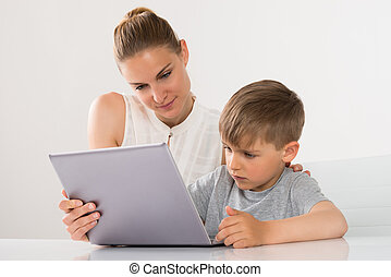 Mother And Son Using Laptop - Close-up Of Mother And Son...