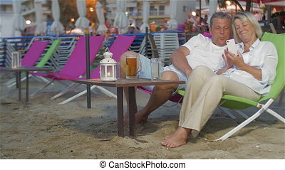 Couple with Smartphone on the Sun Lounger - Mature couple is...