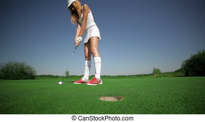 Woman takes the ball from the hole - Young caucasian woman...