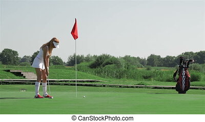 Woman prepares for the putting at the golf - Long shot of...