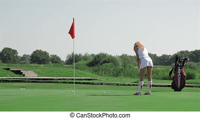 Woman stroke the ball into the hole at the golf - Pretty...