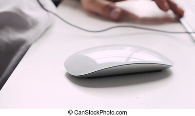 modern mouse on desktop - focus on white mouse, hand coming...