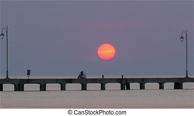 People on the Pier at Sunset - Undefined people are walking...