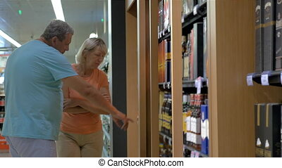 Mature Couple by the Shelf with Alcohol - Mature couple is...