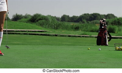 Woman looks at the hole at the golf field - Young caucasian...