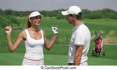 Man talks with woman at the golf - Close up of brownhaired...