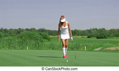 Woman stands on her knee at the golf - Pretty redhead woman...