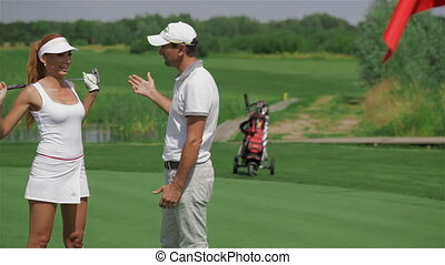 Instructor tells the woman about golf - Attractive male golf...