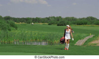 Woman carries a golf bag - Long shot of young redhead woman...