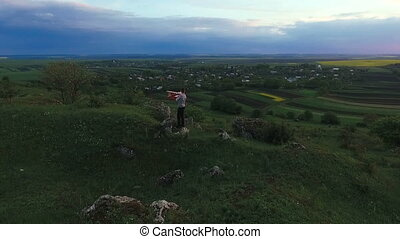 Child hold toy airplane on a green rock over the village. Aerial view