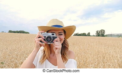 Woman taking photos with retro film camera on the field -...