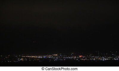 Night city and starting storm - Distant city lights at night...