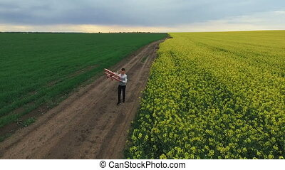 Boy running with toy airplane near the rape fields. Aerial...