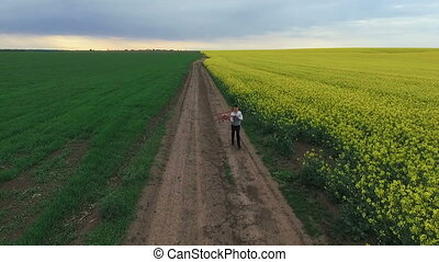 Cheerful child running with toy helicopter near the rape field. Aerial view