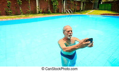 Bearded Old Man Stands in Pool Makes Selfie at Palms -...