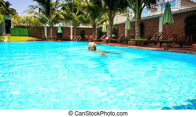 Bearded Old Man Swims in Pool with Palms Brick Fence