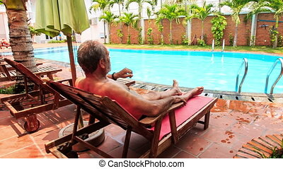 Old Man Rests in Folding Chair by City Swimming Pool -...