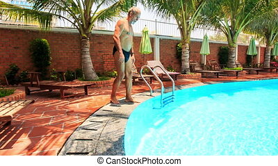 Bearded Old Man Stands up of Chair Dives into Pool -...
