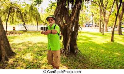 Bearded Old Man in Hat with Bag Makes Selfie in Park -...