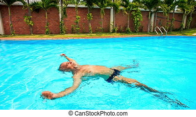 Bearded Old Man Swims on Back along Oval Swimming Pool -...