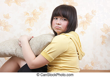 offense - Sad young girl sitting on sofa at home