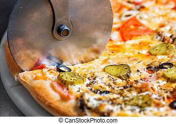 Closeup hand of chef baker in white uniform cutting pizza at kitchen