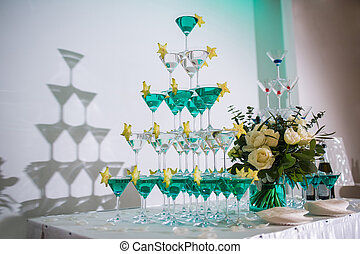 the pyramid of glasses with champagne and a carambola - the...