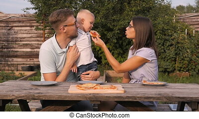 Young Happy Family Having Picnic In The Garden. Mom, Dad And...