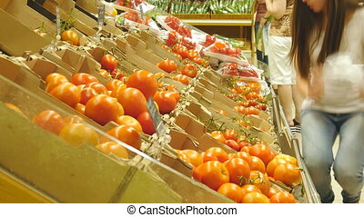 Young pretty girl is choosing tomatoes in a grocery...