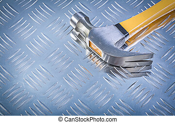 Claw hammer on grooved metal background construction concept