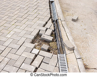 The destruction of the pedestrian walkway of paving with...