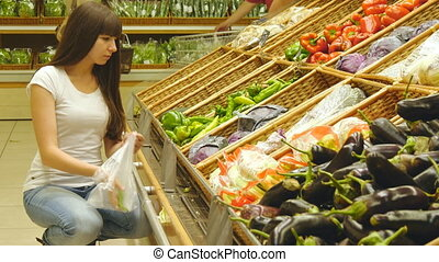 Young pretty girl is choosing peppers in a grocery supermarket.