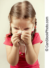 girl wipes her nose with a tissue - Little girl wipes her...